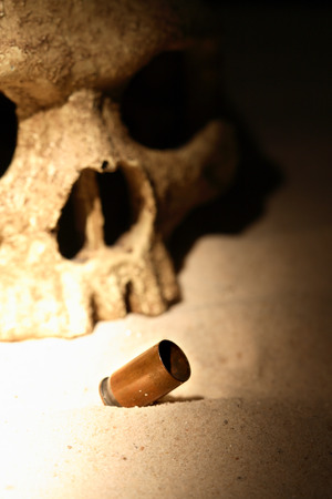 terribly: War concept. One human skull near empty cartridge on sand background