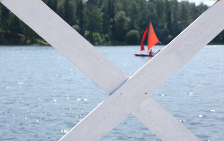 away from it all: View of summer lake with red sail through white wooden fence