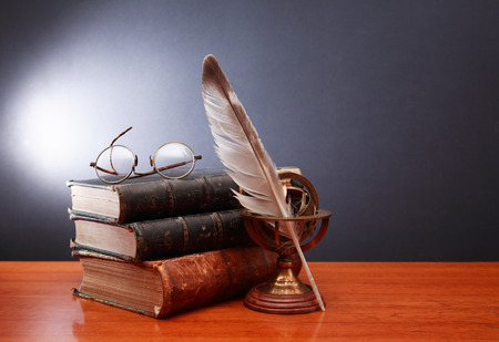 persona leyendo: Vintage still life with quill pen near book and spectacles on dark background