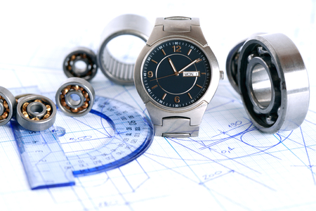 workday: Engineering concept. Few ball bearings near ruler and wristwatch on graph paper background Stock Photo