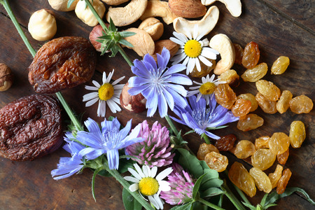 dry food: Dried fruits and nuts near wildflowers on wooden board