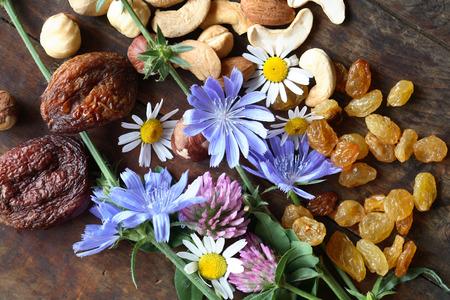 frutas secas: Las frutas secas y nueces cerca de flores silvestres en la tabla de madera Foto de archivo
