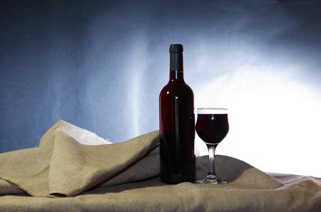 mamadera: Naturaleza muerta con botella de vino tinto cerca de copa de vino en la lona Foto de archivo