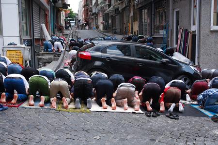 Istanbul, Turkey - July 10, 2015: Muslim men praying on the street