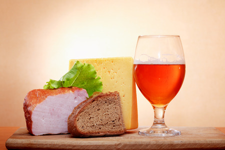 near beer: Glass of beer near cheese and meat against wall with spot of light