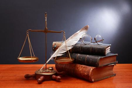 balanza de laboratorio: Cerca de los libros escala de peso de latón antiguo y plumas sobre fondo oscuro