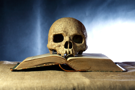 poem: One human skull on old open book against dark background