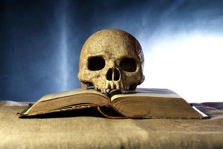 open agenda: Un cráneo humano en el viejo libro abierto contra el fondo oscuro