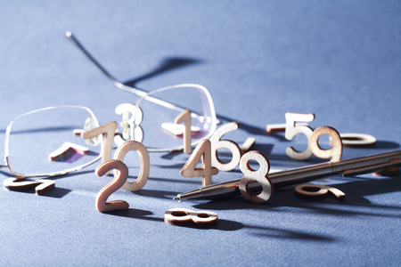 bookkeeping: Set of wooden digits near pen and spectacles on gray background Stock Photo