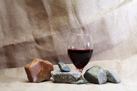 goblet: Goblet with red wine near stones on canvas background