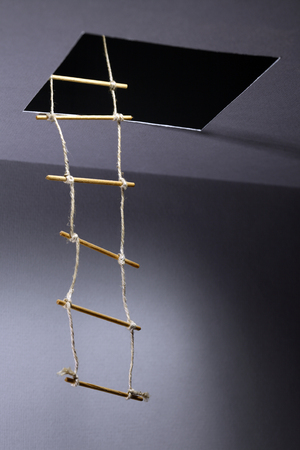 away from it all: Rope ladder inside hatch in ceiling Stock Photo