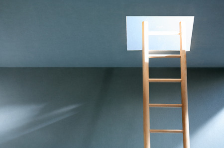 suspenso: Escala de madera en la habitación vacía con pasa-platos iluminado en el techo Foto de archivo