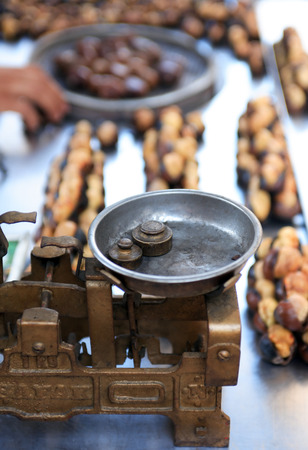 conkers: Roast chestnut sale. Closeup of vintage scales near roasted chestnuts on stall