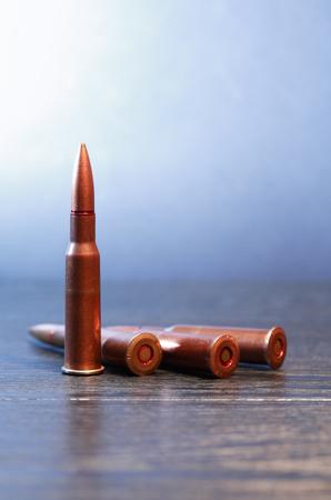 gun shell: Pocas cartuchos de rifle en superficie de madera contra el fondo gris