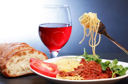 Traditional Italian supper. Plate with Bolognese pasta near red wine and bread Stock Photo