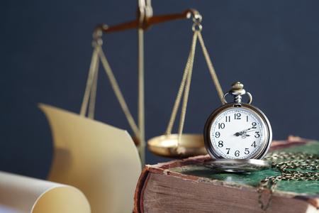 balanza de laboratorio: Bodegón vintage. Reloj de bolsillo en el libro antiguo, cerca de la escala de peso