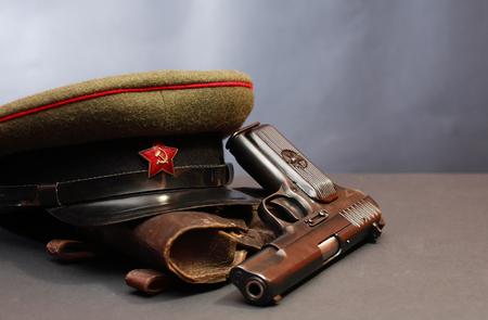 wojenne: World War II Soviet officer equipment. Military cap near handgun and holster Zdjęcie Seryjne