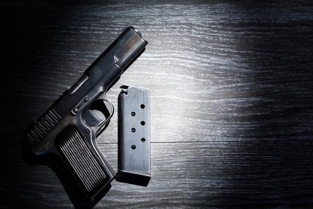 Crime concept. Handgun near holder on dark wooden background under beam of light