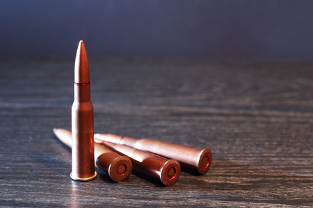 acute angle: Few rifle cartridges on wooden surface against gray background