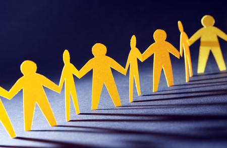 統合概念。暗い背景上の行の黄色い紙男性