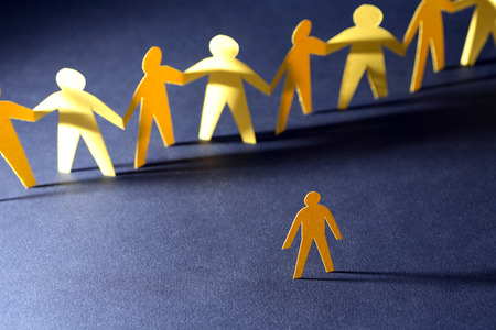 Confrontation concept. Yellow paper man against crowd in a row on dark