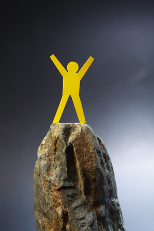 attainment: Yellow paper man standing on the rock against dark background