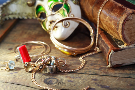 antifaz: Set of jewelry near carnival mask and old books
