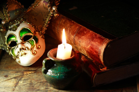 antifaz: Art concept. Vintage still life with old books near Venetian mask and lighting candle Foto de archivo