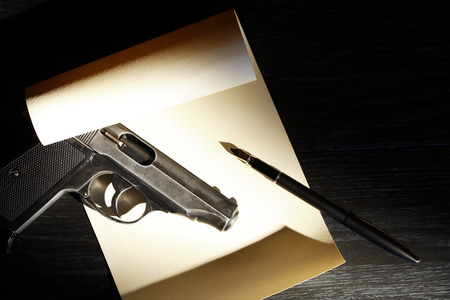 dying: Dying Message. Handgun and pen on blank paper sheet Stock Photo