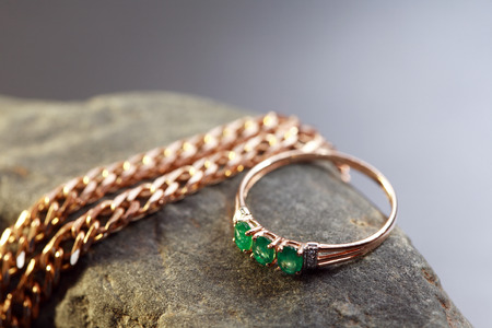 emerald stone: Gold ring with emerald near chain on gray stone against nice dark background Stock Photo