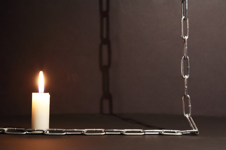 dungeon: Dungeon concept. Lighting candle near metal chain on dark background Stock Photo