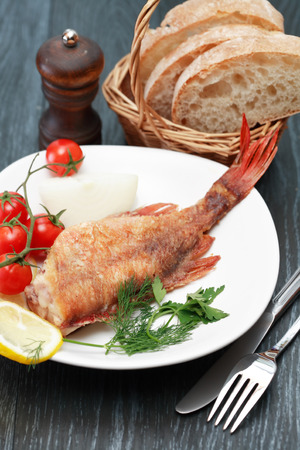 mediterranean cuisine: Mediterranean cuisine. Plate with fried fish and vegetables near fork and knife