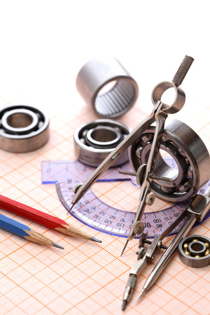 graph paper: Industrial concept. Drawing instrument near ball bearings on graph paper background Stock Photo