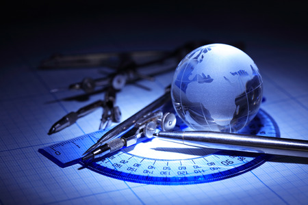 drawing instrument: Education concept. Drawing instrument near glass globe on graph paper