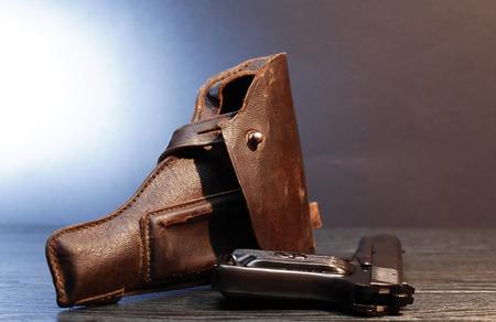 holster: Old leather handgun holster and pistol on dark background