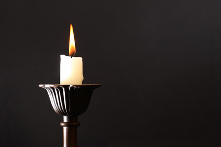 lighting background: Lighting candle in candlestick on dark background Stock Photo