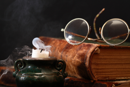 smoke background: Vintage still life. Spectacles on closed book near extinguished candle