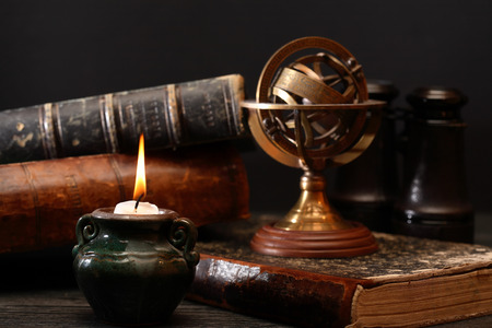 Ancient astrology. Old astrology globe and books near lighting candle