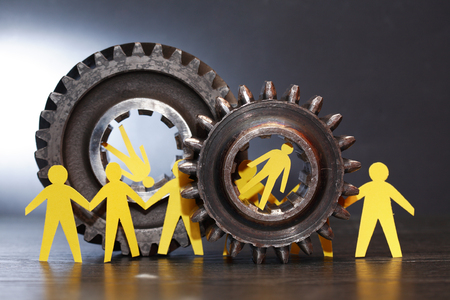 inhibition: Under pressure. Yellow paper men inside old metal gears on dark background