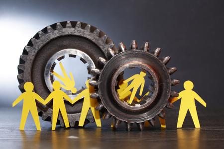 totalitarianism: Under pressure. Yellow paper men inside old metal gears on dark background