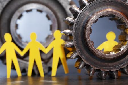 totalitarianism: Yellow paper men inside old metal gears on dark background