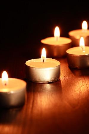 lighting background: Set of lighting candles on wooden board against dark background