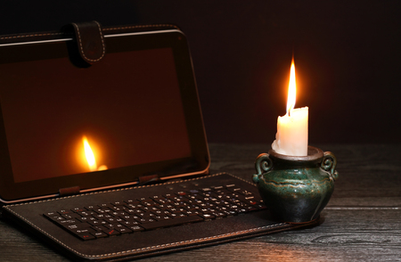 Blackout concept. Lighting candle near laptop with dark empty screen