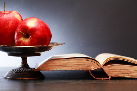 Still life with open old book near red apples in vintage fruit bowl Stock Photo
