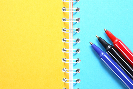 yellow background: Three various pens on notebook with colored blank pages Stock Photo