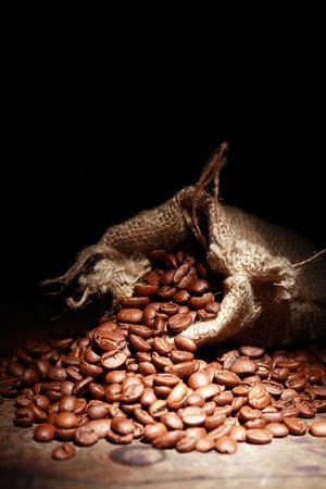 jute sack: Primo piano di sacco di iuta pieni di chicchi di caffè su sfondo scuro