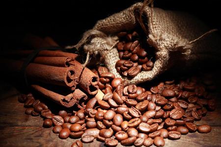 jute sack: Jute sack with coffee beans near cinnamon on dark background