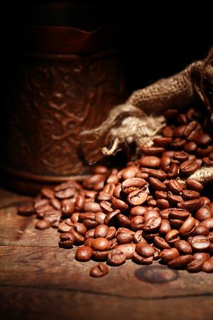 sacco juta: Primo piano di sacco di iuta pieni di chicchi di caffè su sfondo scuro