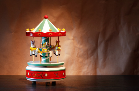 Vintage wooden toy carousel horses against crumpled paper background