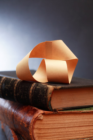 topology: Paper Mobius strip on old books against dark background Stock Photo
